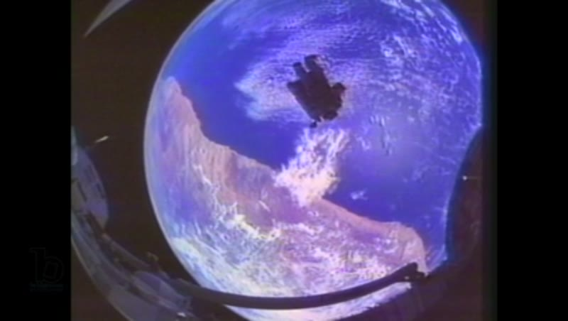 1980s: Fisheye view of astronaut floating across docking bay of Space Shuttle with earth behind them