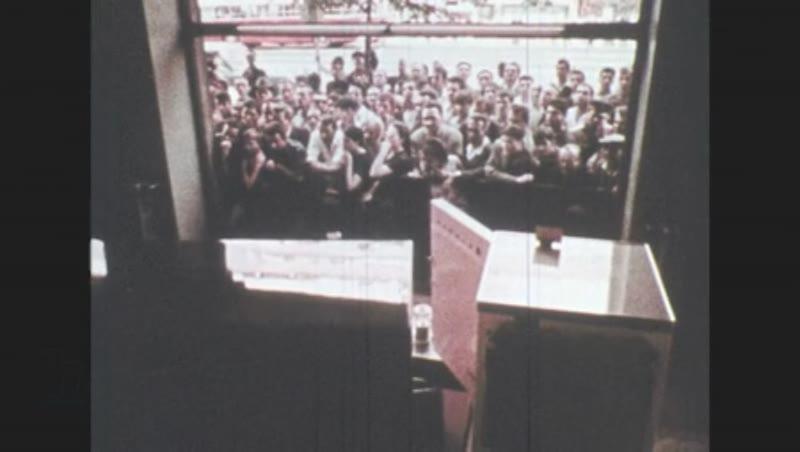 1970s: Crowd in street looks in store window