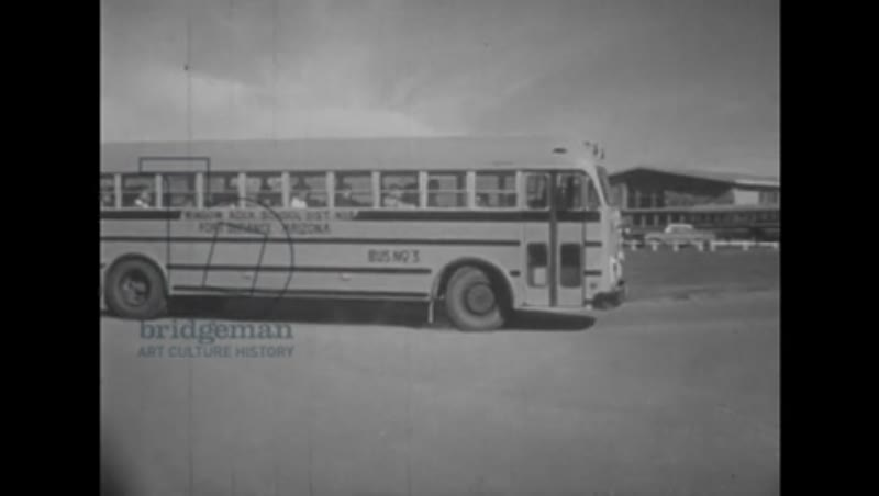 1950s: UNITED STATES: Window rock School sign. School bus drives to school. Children arrive at school