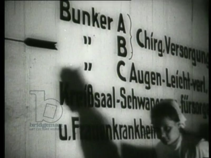 German pilots run to their airplanes, one pilot connects a camera to the wing of his airplane. Patients in a hospital are brought to a bunker. The movements of the airplanes are carefully observed