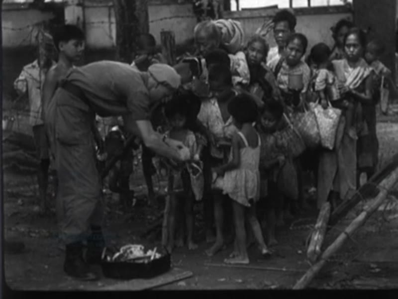 Dutch soldiers hand out food to children in Palembang, Indonesia.
