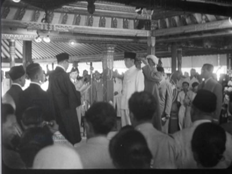 Sukarno, on stage, takes the oath and becomes the first President of independent Indonesia
